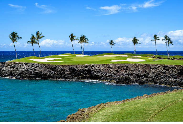 Golf course in Hawaii with ocean and palm trees